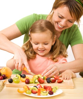 Woman and little girl preparing fruit salad